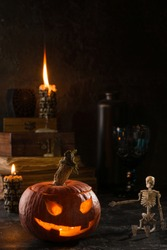 Vintage halloween still life  with candles, antique books, halloween pumpkin and skeleton. Dark photo.
