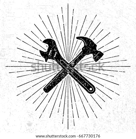 Vintage hammer and spanner symbol with sun burst