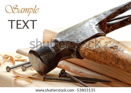 Vintage hammer with nails and wood on white background with copy space.  Macro with shallow dof.