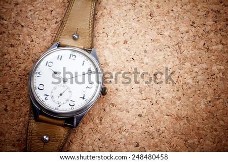Vintage hand watch on cork-board background.