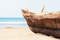 Vintage handmade fisherman boat with fishing nets on the beach near the ocean in Arambol, Goa, India. Sandy coastal of the Arabian Sea, concept travel, tropical resort, vacation in paradise places