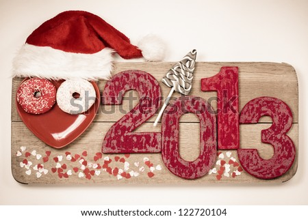 Vintage handmade New Year 2013 snake date with Santa hat on wooden board