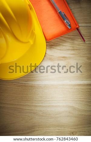 Vintage hard hat notepad pen on wooden board. - Shutterstock ID 762843460