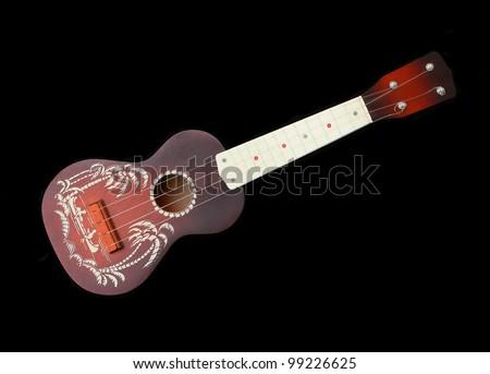 Vintage hawaii ukulele guitar isolated against black background