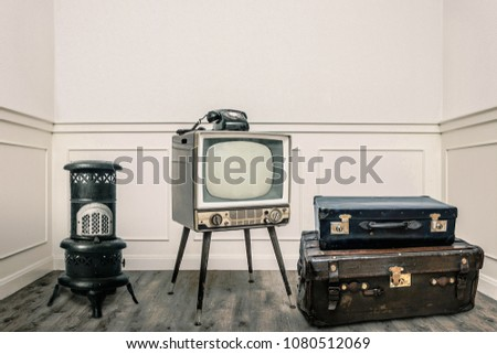 Vintage heater, television, and suitcases on floor in cozy room #1080512069