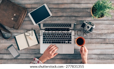 Vintage hipster wooden desktop top view, male hands using a laptop and holding a cup of coffee #277831355