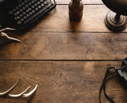 Vintage Hipster Wooden Table Desk Background Texture Great for Display and Mockup with Old Camera, Black Typewriter, Bronze Lamp, White Deer Antlers and Old Retro Bottle