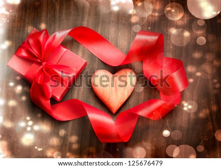 Vintage Holidays gift with a bow from ribbon and heart on wooden background/Valentines day background