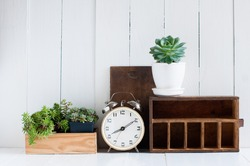 Vintage home decor: old wooden boxes, houseplants, alarm clock on white wooden board, retro home interior.