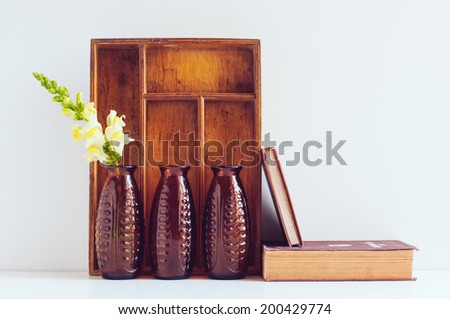 Vintage home decor, three brown glass flower vases, wooden box and old books on a white background.