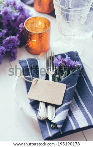 Vintage home table setting with blue napkins, antique cutlery and purple cornflowers on white wooden table. Blank cardboard tag.