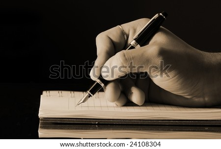 vintage horizontal photo of a man's hand writing into a notebook using a fountain pen