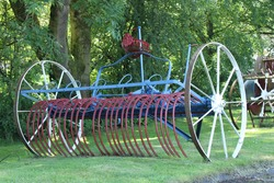 Vintage horse drawn hay rake isolated on grass. Old farming equipment