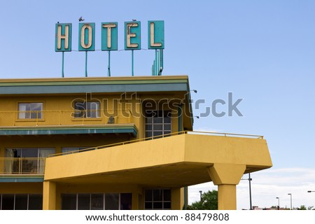 Vintage hotel sign with birds perched on top stands above a colorful motel on the side of the highway.
