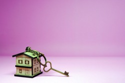 Vintage House key with home keyring on pink background and copy space - New home concept