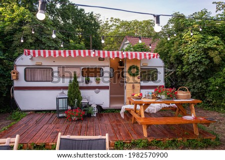 Vintage house trailer for family holidays, budget travel. On the wooden porch there is table with benches for food, on the lawn there is lounger for sunbathing. Track decorated with garland of lamps Stock photo ©