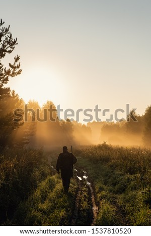 Vintage hunter walks the forest road. Rifle Hunter Silhouetted in Beautiful Sunset or Sunrise. Hunter aiming rifle in forest