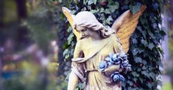 Vintage image of a sad angel against the background of leaves (fragment)