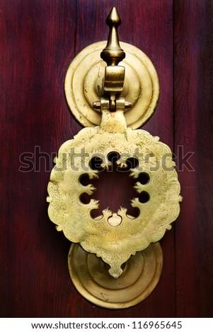 Vintage image of ancient door knocker on a wooden door.