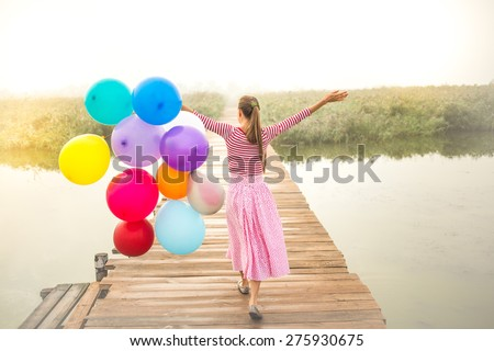 Vintage image of beautiful woman with colorful balloons walking on wooden bridge. grain added, in motion