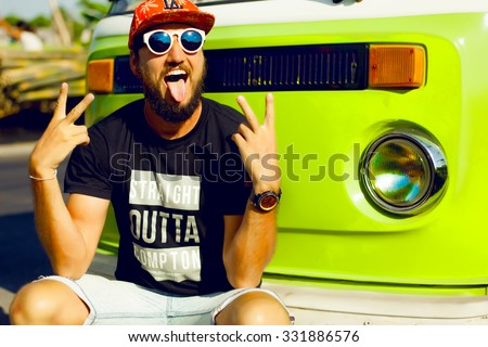 vintage image of hipster man hiker,casual hipster outfit,cap and big sunglasses,bearded man outdoors,toned,retro style,peace sign,hippie man,surfer man having fun,reflecting sunglasses,retro bus
