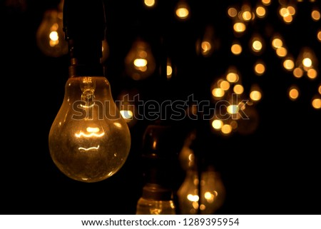 Vintage incandescent light bulbs lit in the dark.