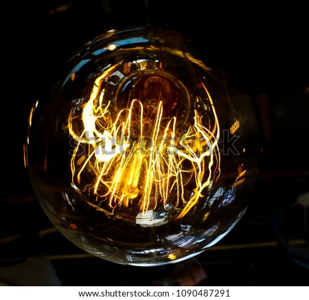 Vintage Industrial Filament Lightbulb Light hanging in black background #1090487291
