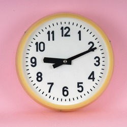 Vintage industrial wall clock. Analog white clock. Retro antique clock in bright pink color background isolated.