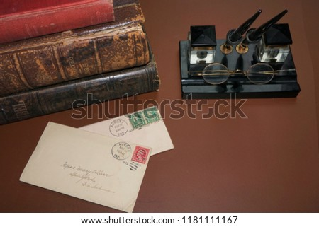 Vintage ink well pen, wire-framed glasses, old books and letters with room for copy space #1181111167
