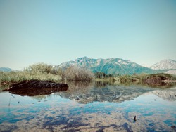 Vintage inspired photo taken at the world renowned Lake Tahoe. Beautiful photo of a mountain-scape reflecting off still waters.