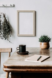 Vintage interior design of kitchen space with small table against white wall with simple chairs, notebook, herbs and vegetables. Minimalistic concept of kitchen space on country side. Natural climat.