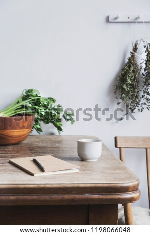 Vintage interior design of kitchen space with small table against white wall with simple chairs, notebook, herbs and vegetables. Minimalistic concept of kitchen space.
