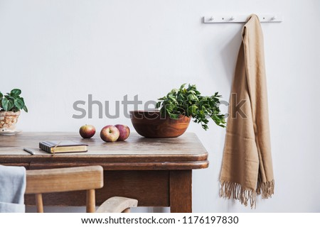 Vintage interior design of kitchen space with small table against white wall with simple chairs and vegetables. Minimalistic concept of kitchen space.