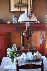 Vintage interior of the living room. An ancient chandelier hangs over the dining table, on which there is a tea set.