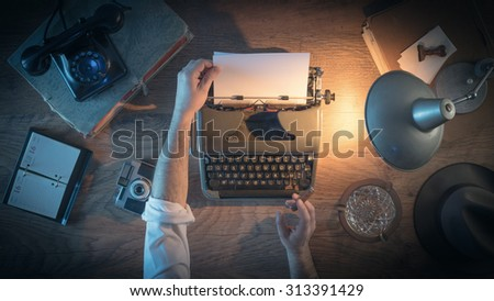 Vintage journalist\'s desk 1950s style, he is working and typing on his typewriter late at night, top view