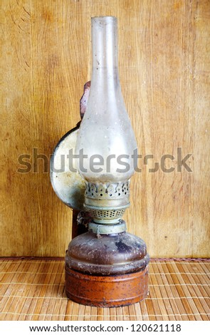 Vintage kerosene lamp on table over wooden background