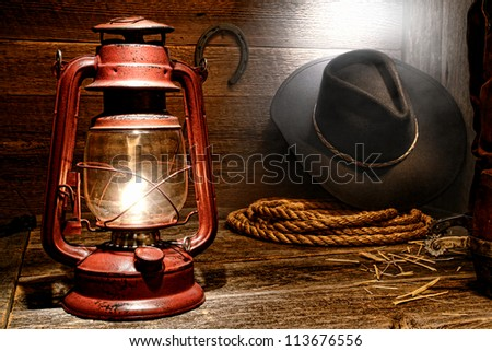 Vintage kerosene lantern lamp with American West rodeo cowboy gear with hat and ranching lasso rope near authentic leather roping boots in soft window light diffused in smoke in an old ranch wood barn
