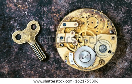 Vintage key and gold watch clockwork mechanism, gears, timing, time management concept
