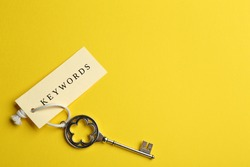 Vintage key and tag wIth word KEYWORDS on yellow background, top view. Space for text