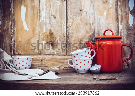 Vintage kitchen decor, red enamel coffee pot and cups with polka dots on an old wooden board background with copy space. Rustic home decor.