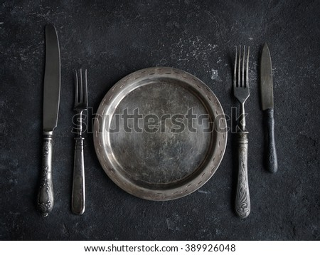 Vintage kitchen utensils on a background of black stone, plate, knife and fork