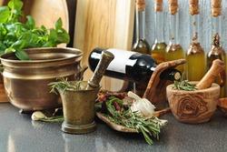 Vintage kitchen utensils with Basil and bottles of olive oil.