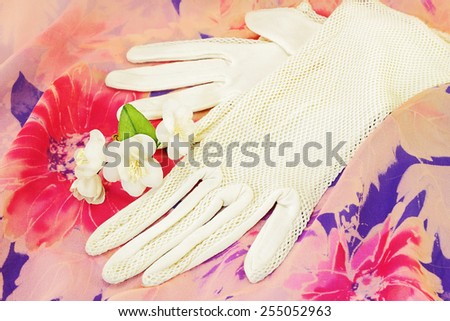 Vintage lace gloves and artificial flowers of jasmine on vintage textile