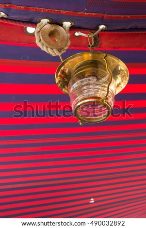 Vintage lamp below red and blue striped awning on the training sailing barquentine