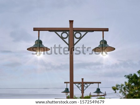 Vintage lamp post with illuminated light bulbs.             #1572549679