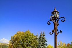 Vintage Lamppost against Fall Foliage and Vivid Blue Clear Sky