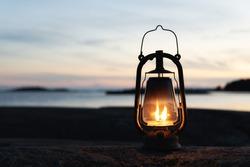 Vintage lantern at sunset, romantic evening at the beach. Mystical scene with old kerosene lamp. Copy space.