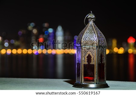 Vintage lantern. Ramadan mood at night with light of Doha city in the background. #550619167