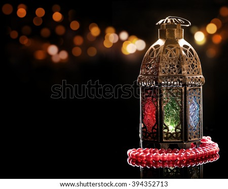 Vintage lantern with red rosary.\Ramadan mood at night with light decoration in the background.