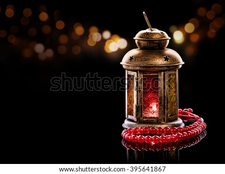 Vintage lantern with red rosary.\ Ramadan mood at night with light decoration in the background.